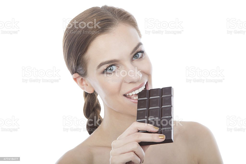 Portrait of a beautiful young woman eating chocolate bar. royalty-free stock photo