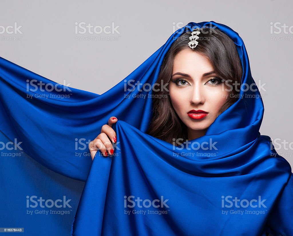 Portrait of a beautiful young woman in blue fabric stock photo