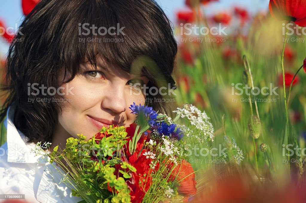 portrait of a beautiful young woman in poppy field royalty-free stock photo