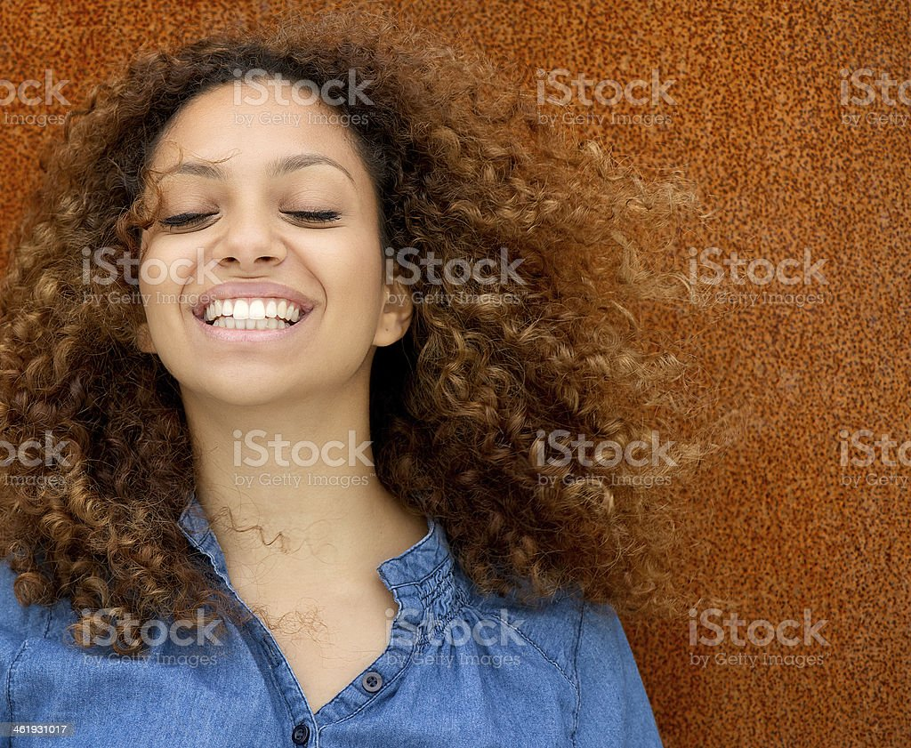Portrait of a beautiful young woman laughing with curly hair stock photo