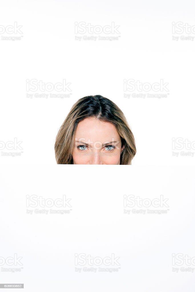 Portrait of a beautiful young woman peeking behind whiteboard stock photo