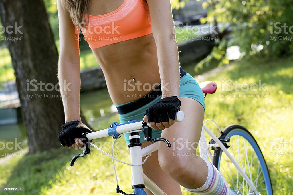Portrait of a beautiful young woman with her bike outdoor stock photo