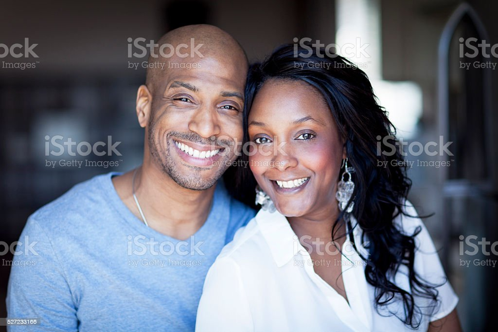Portrait Of A Black Couple Smiling At The Camera At Home stock photo