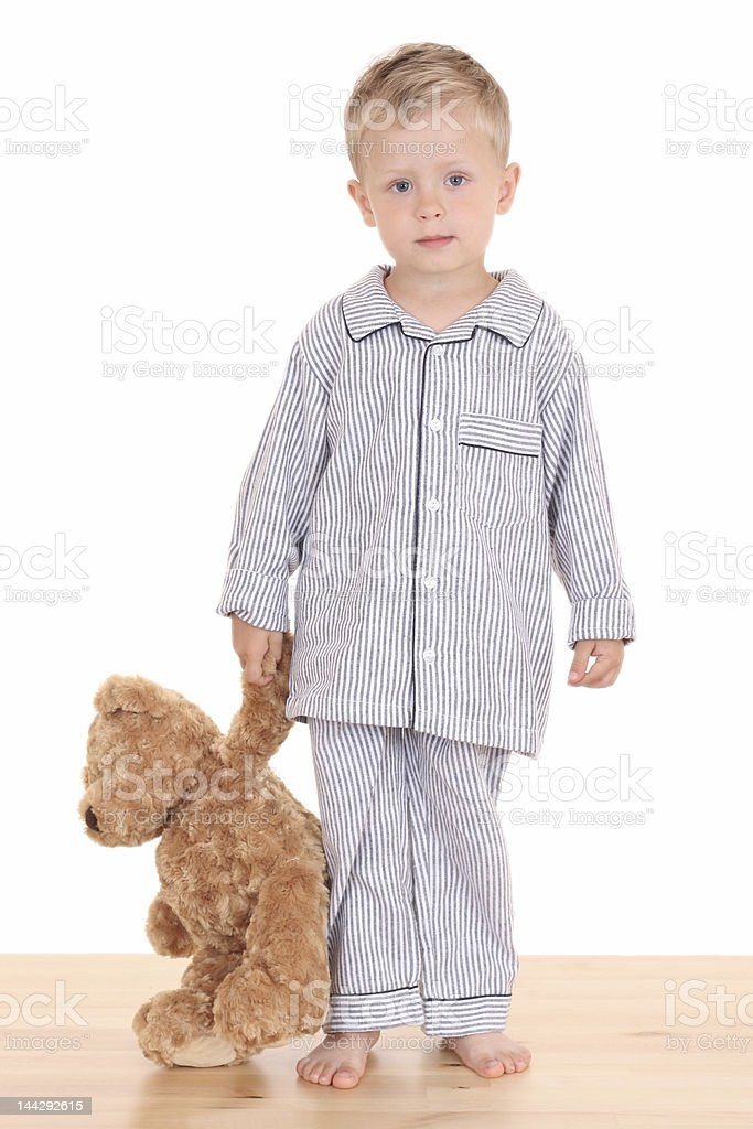 Portrait of a blond boy with a teddy bear ready to go to bed stock photo