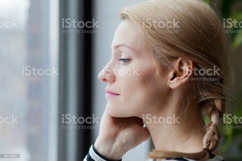 Portrait Of A Blond Woman At The Window stock photo