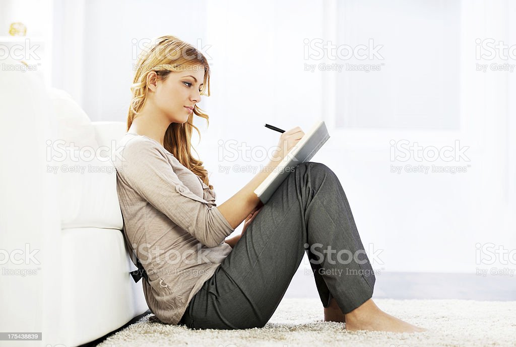 Portrait of a blonde woman writing diary. stock photo
