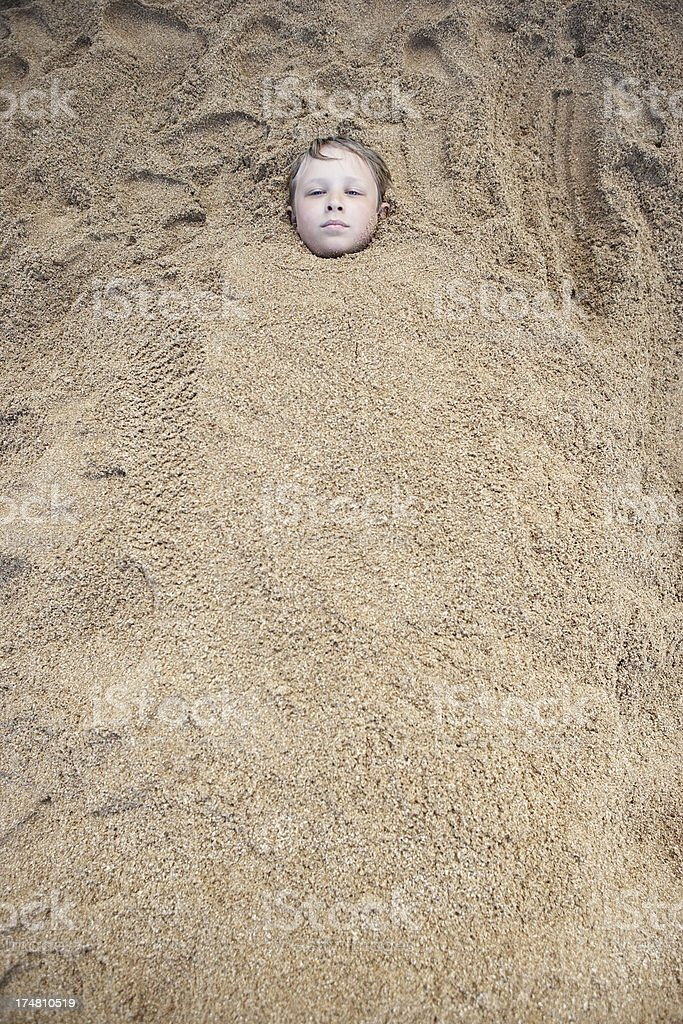 Portrait of a boy buried in sand stock photo