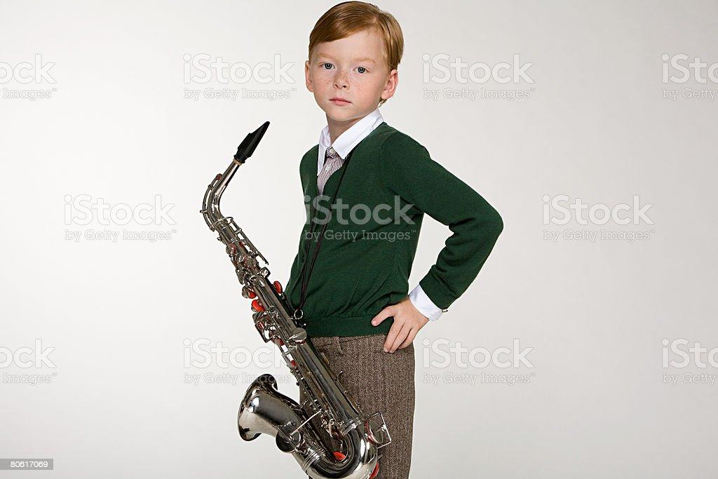 A portrait of a boy holding a saxophone stock photo