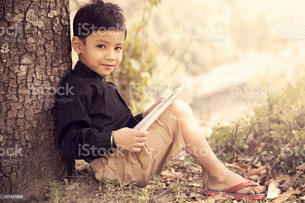 Portrait of a boy sitting under tree and reading book stock photo