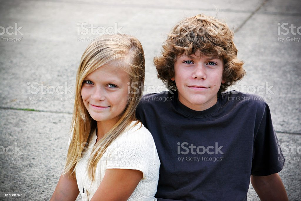 Portrait of a brother and sister sitting on pavement stock photo