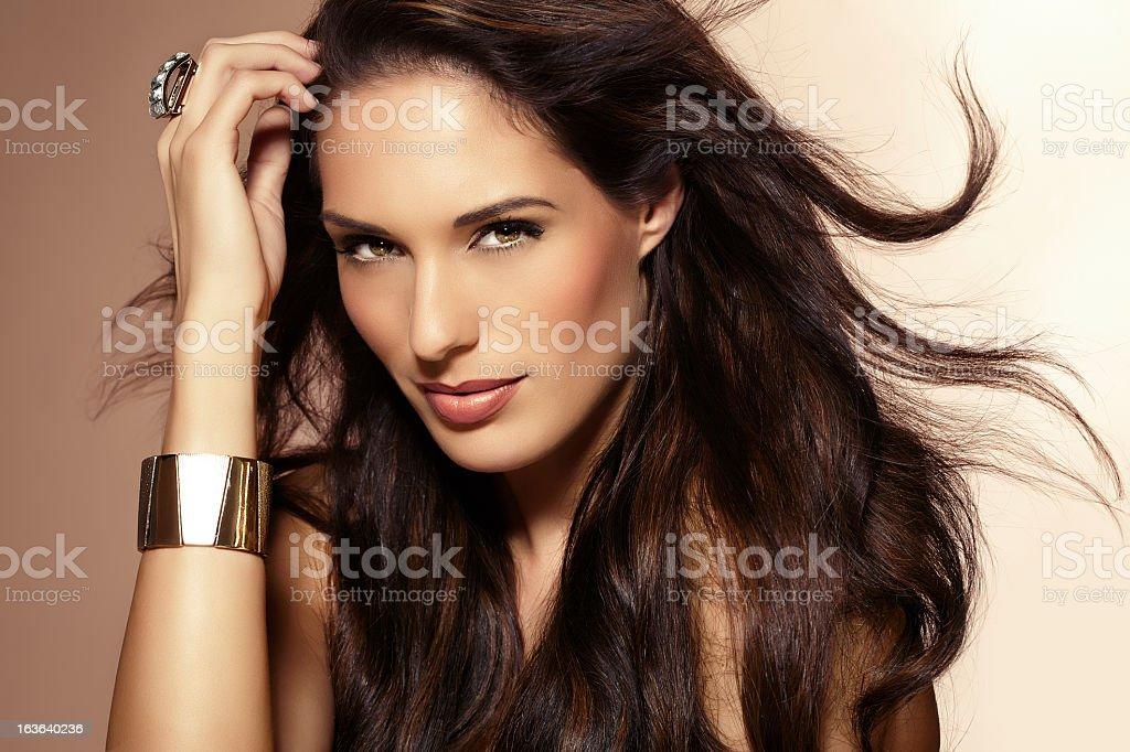 Portrait of a brunette woman wearing a gold bracelet royalty-free stock photo