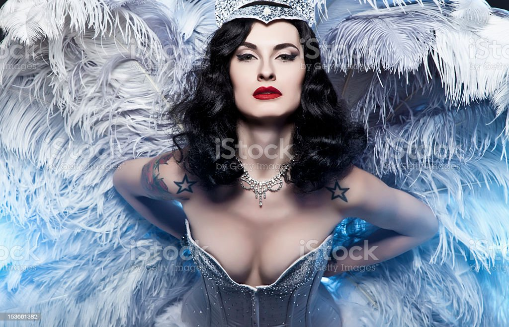 Portrait of a burlesque diva in a blue bustier and feathers stock photo