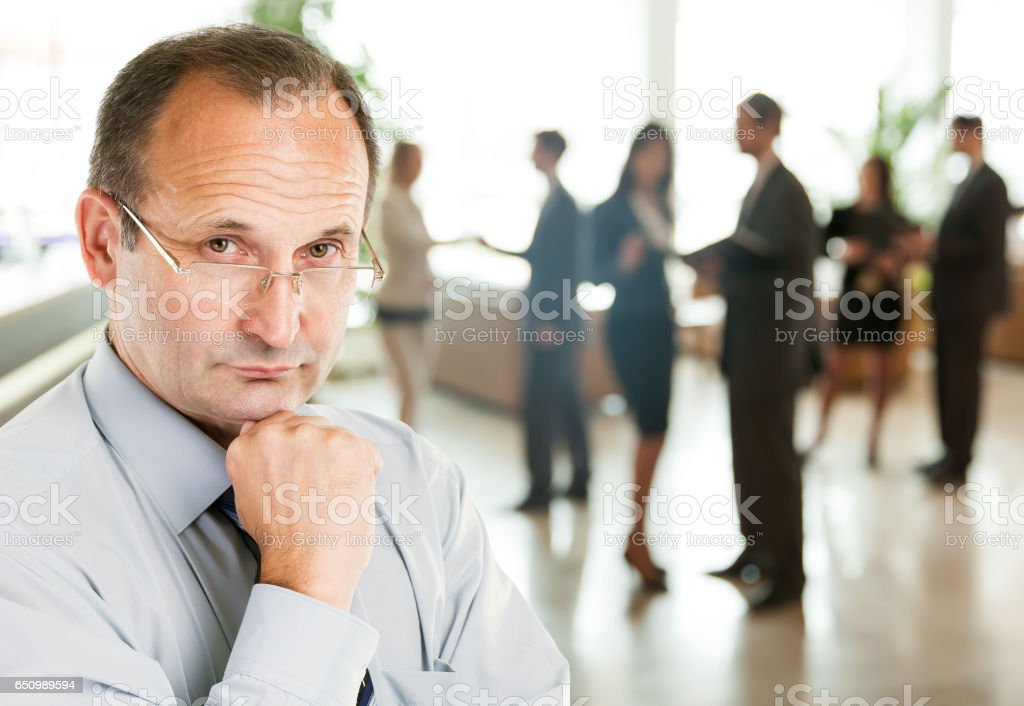 Portrait of a businessman psychologist - consultant on the background large team working stock photo
