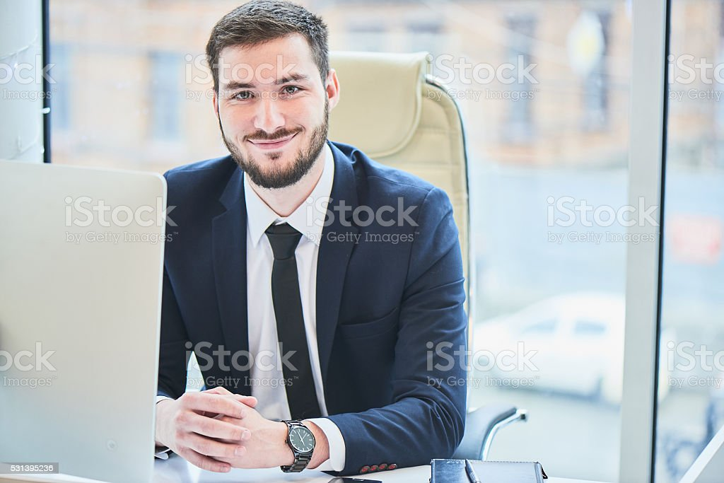 Portrait of a businessman sitting on the workplace stock photo