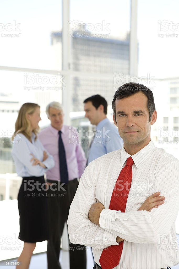 Portrait of a businessman with Managers talking in the background royalty-free stock photo