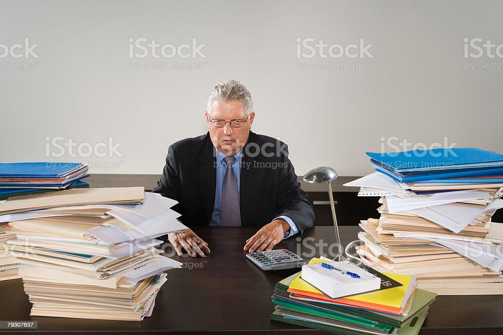 Portrait of a businessman with stacks of files stock photo