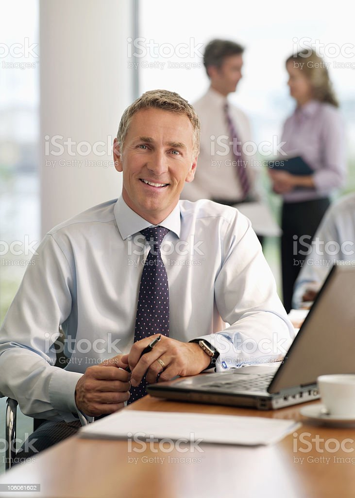 Portrait of a businessman with three colleagues discussing in the background stock photo