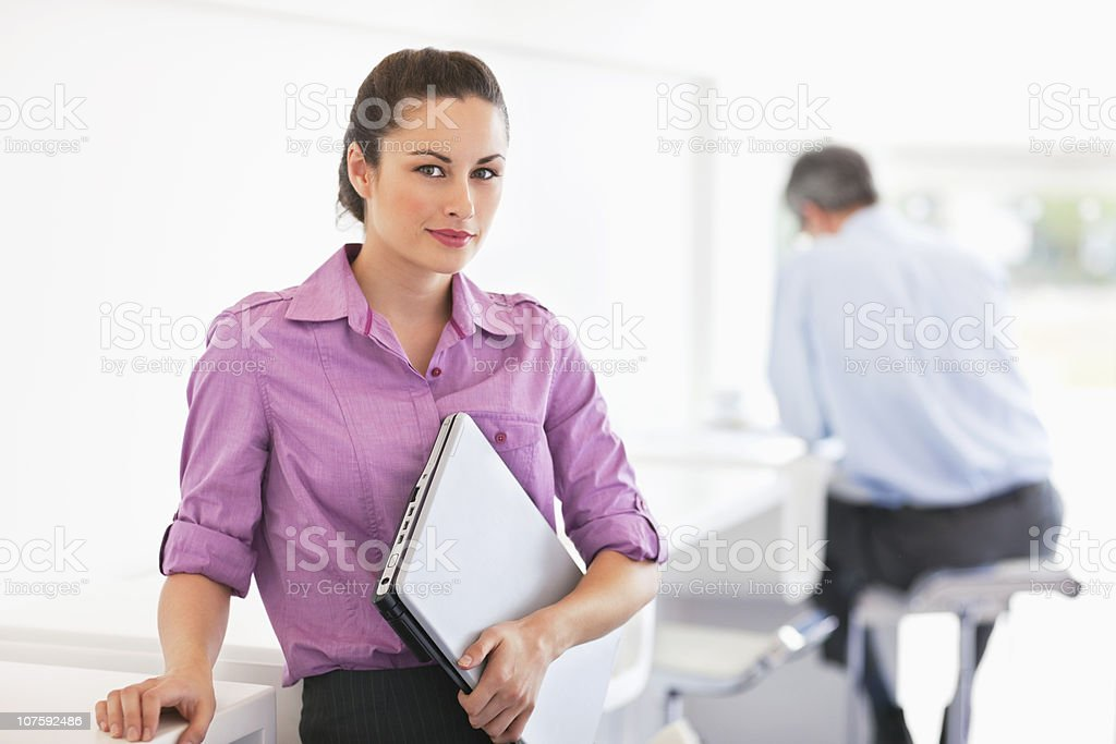 Portrait of a businesswoman carrying laptop with colleague in the background royalty-free stock photo