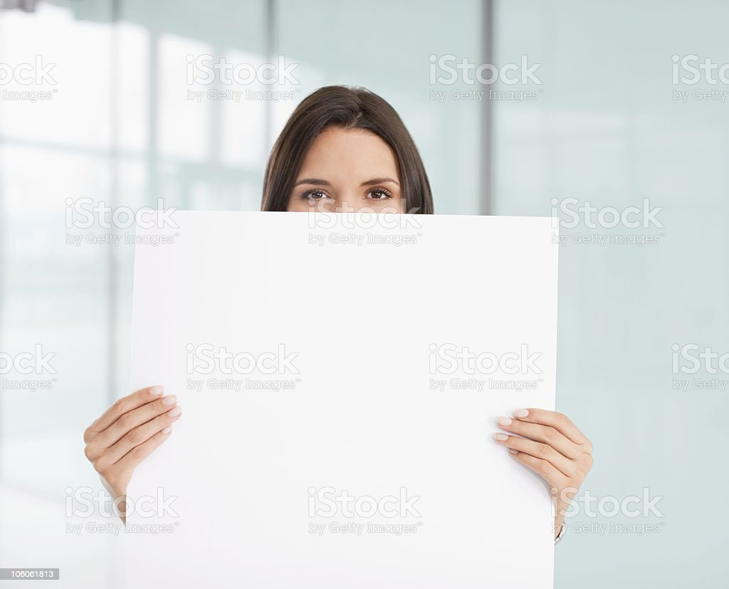 Portrait of a businesswoman holding up blank white paper stock photo