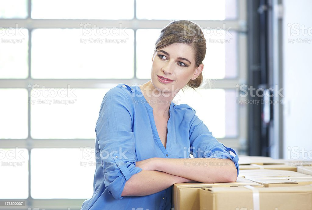 Portrait of a businesswoman relaxing next to boxes in warehouse royalty-free stock photo