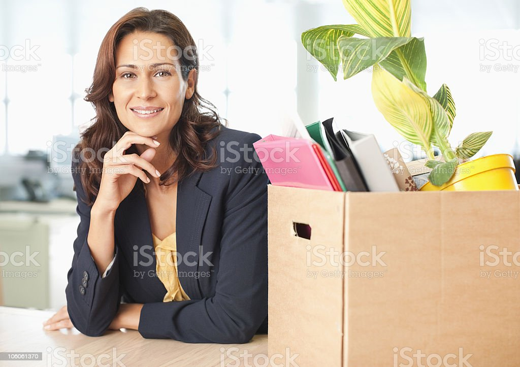 Portrait of a businesswoman with cardboard box of office items royalty-free stock photo