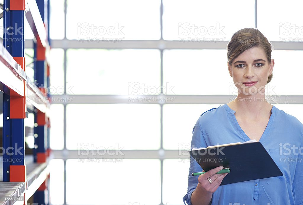 Portrait of a businesswoman with clipboard in warehouse royalty-free stock photo
