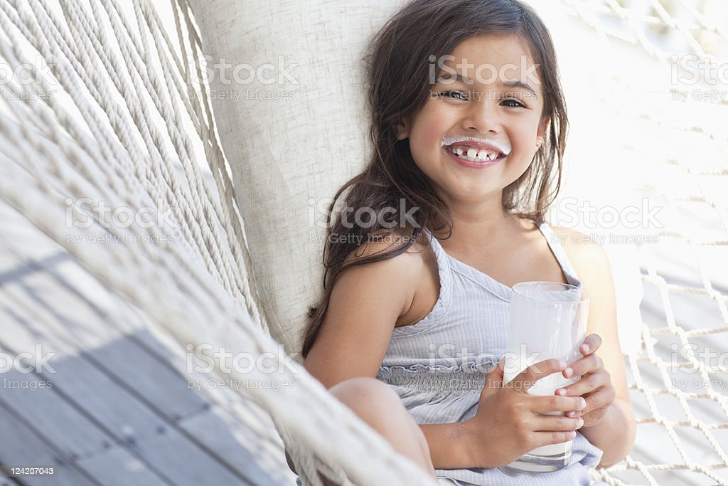 Portrait of a cheerful cute girl smiling holding a glass of milk royalty-free stock photo