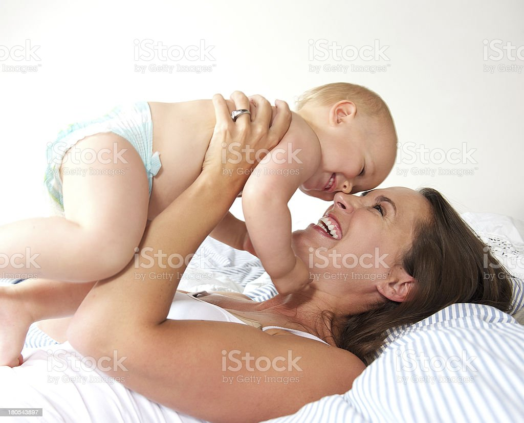 Portrait of a cheerful mother and cute baby playing stock photo