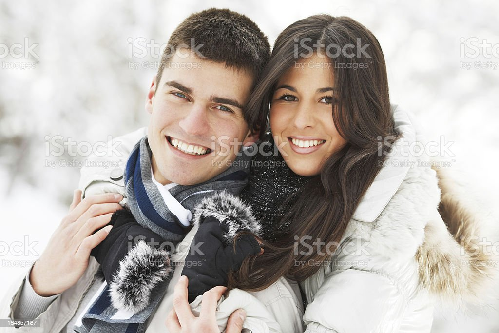 Portrait of a cheerful teenage couple surrounded by snow. royalty-free stock photo