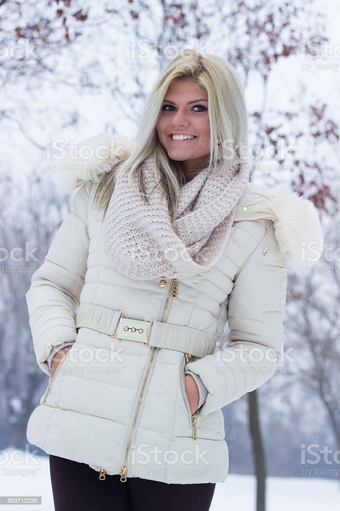 Portrait of a cheerful teenage surrounded by snow stock photo