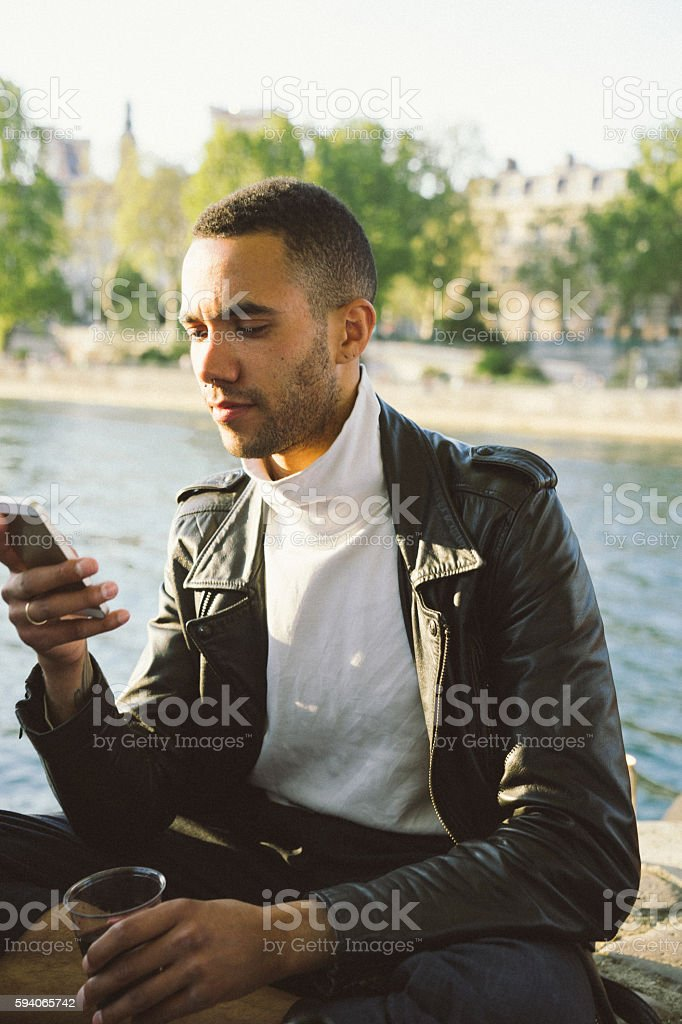 Portrait of a cheerful young man looking at his smartphone stock photo