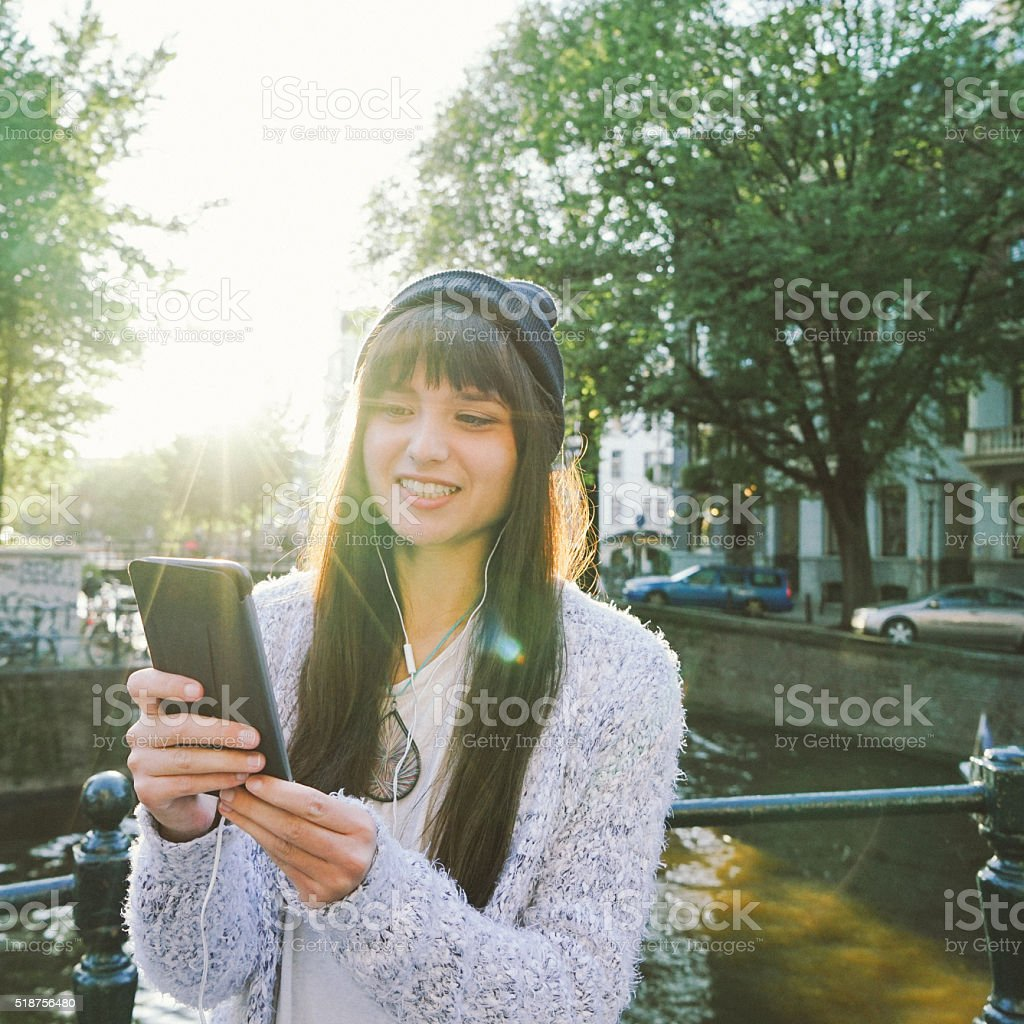 Portrait Of A Cheerful Young Woman Texting stock photo