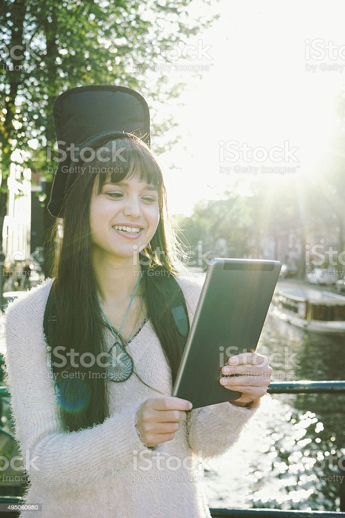 Portrait Of A Cheerful Young Woman Using Digital Tablet stock photo