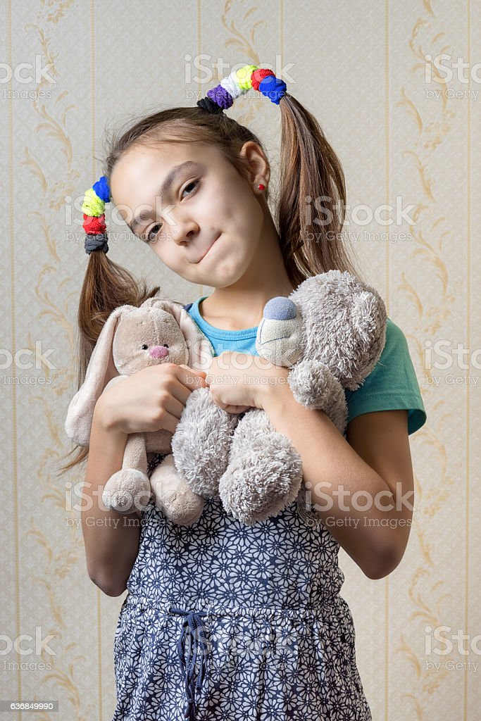 portrait of a child biting her lip with soft toys stock photo