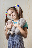 portrait of a child biting her lip with soft toys