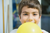 Portrait of a child blowing up yellow balloon