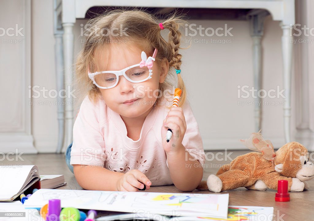 Portrait of a child in glasses with markers. stock photo