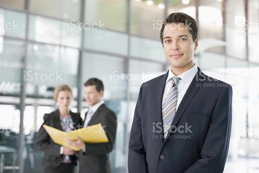Portrait of a confident businessman with people discussing in the background royalty-free stock photo