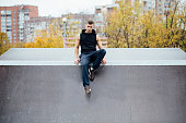 Portrait of a confident fitness guy. Man poses on skate
