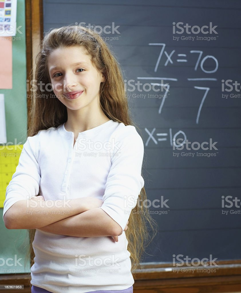 Portrait of a confident girl with hands crossed against blackboard royalty-free stock photo