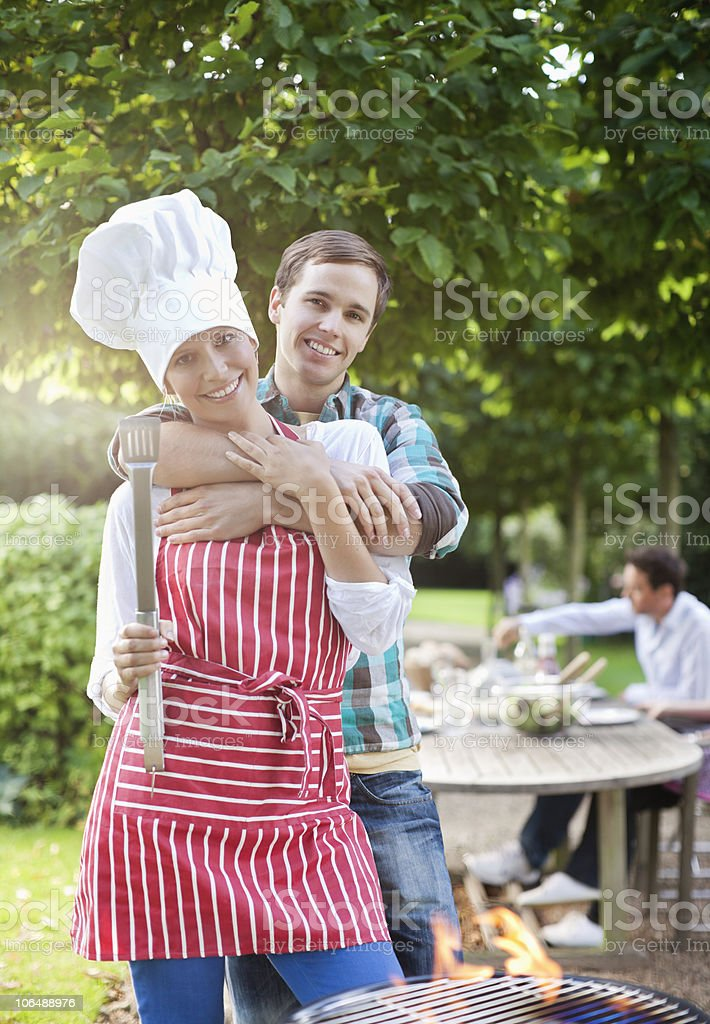 Portrait of a couple standing by barbecue in garden, smiling royalty-free stock photo