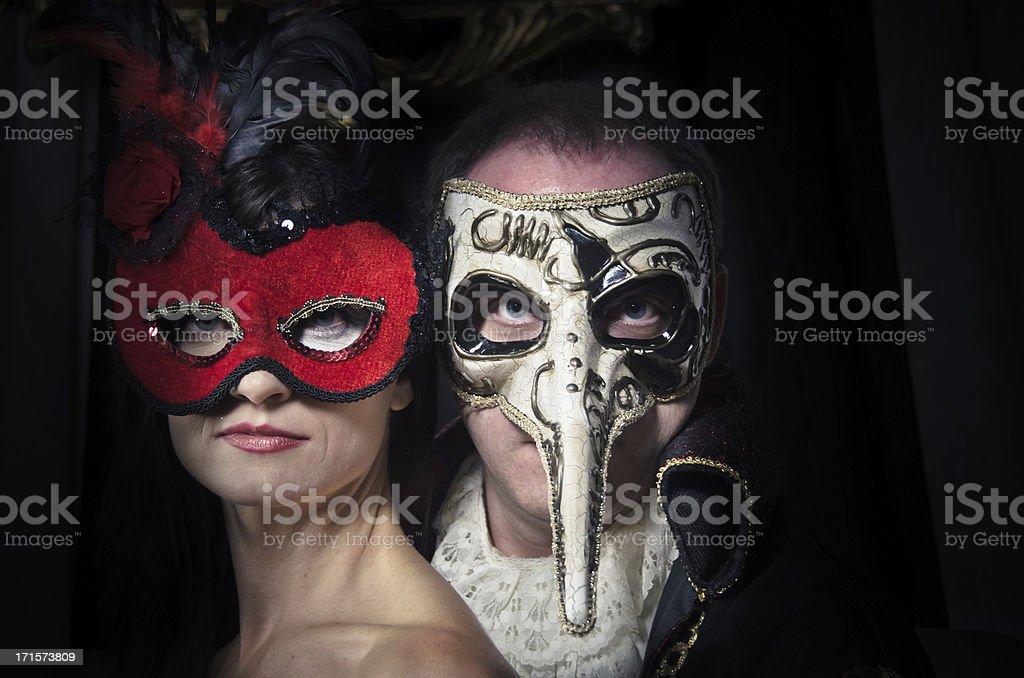 Portrait of a Couple Wearing Venetian Masks stock photo