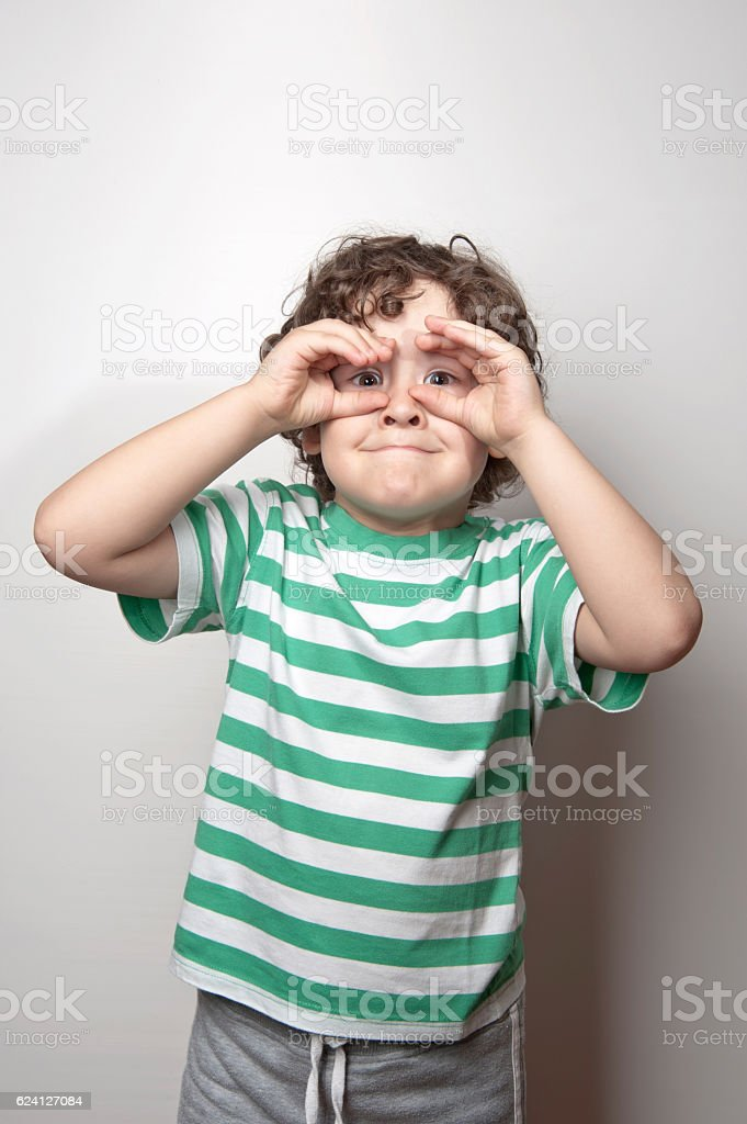 Portrait of a cute boy making binoculars with his hands stock photo