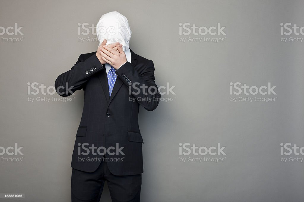 portrait of a faceless man covering his mouth stock photo