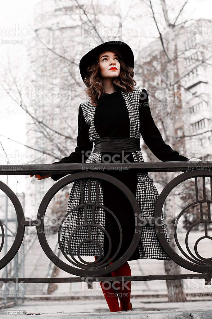 Portrait of a fashionable woman standing on a bridge royalty-free stock photo