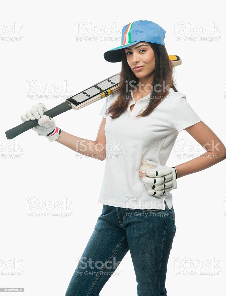 Portrait of a female cricket fan holding a bat stock photo