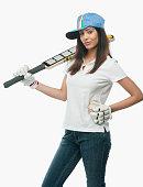Portrait of a female cricket fan holding a bat