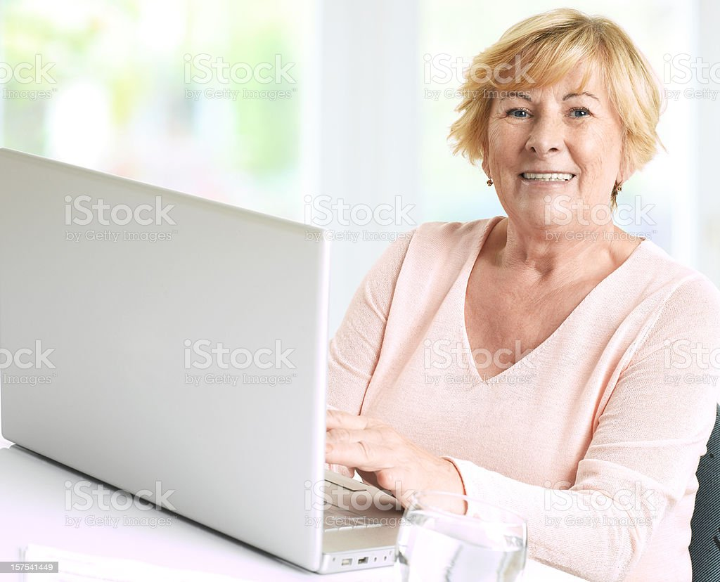 Portrait of a female senior working on her laptop computer stock photo
