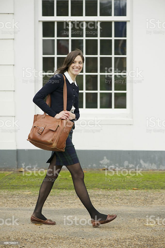 Portrait of a female student walking outdoors with bag royalty-free stock photo