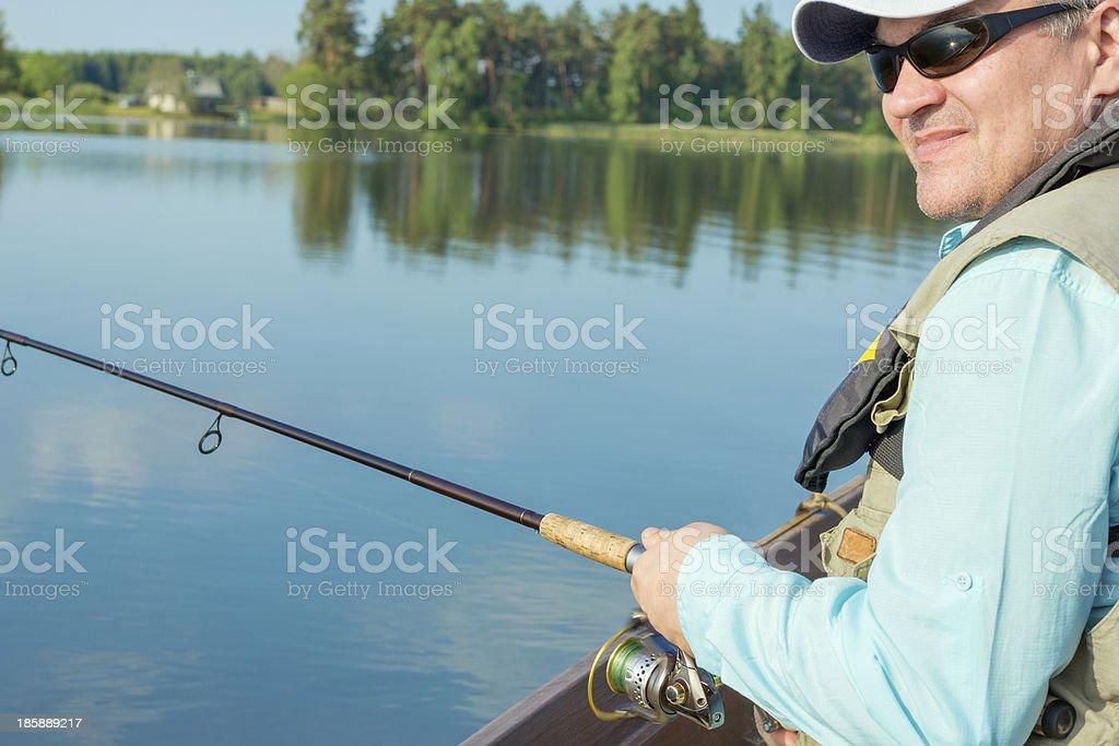 Portrait of a fisherman fishing on a lake stock photo